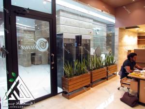 طراحی داخلی سبز کافه ویونا سعادت آباد فلاورباکس چوبی داخلی سانسوریا
