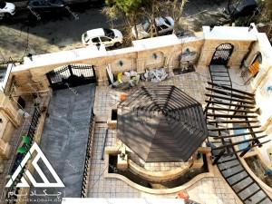 نمایی بالا از آلاچیق تک پایه چوبی چوب پلاست در حیاط ساختمان مسکونی زرافشان