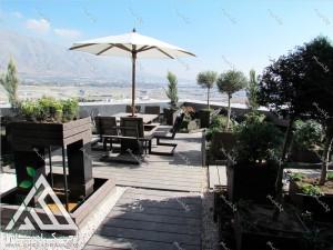 طراحی فضای سبز تراس کرج پس از اجرا شامل فلاورباکس گل درخت گلدان چتر و میز و نیمکت محوطه و آبنما راهروی چوبی
