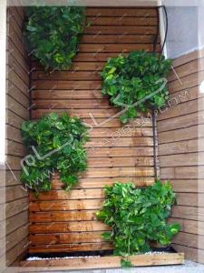 نمای تراس سبز تجریش ترکیب چوب ترمووود و گل و گیاه در گلدان دیواری