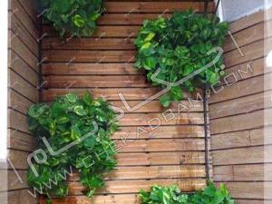 نمای ترکیب چوب ترمووود و گل و گیاه در گلدان دیوار تراس سبز تجریش