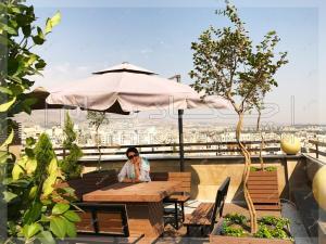 میز و نیمکت و چتر آفتابی روی پشت بام