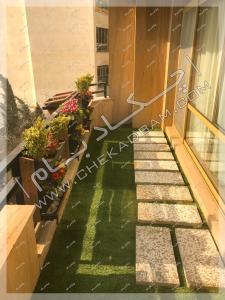 گلدان لبه جانپناه تراس و چمن مصنوعی در تراس سبز کامرانیه تهران